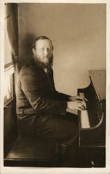 Man in Suit Seated at Piano, Hands on Keys