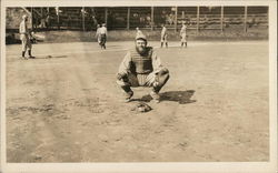 Catcher Crouching with Baseball Players in Background on Field Postcard