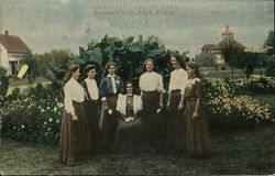 6 Women Standing Around a Woman Sitting in a Chair in a Garden