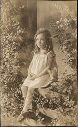 A Little Girl Sitting in a Garden