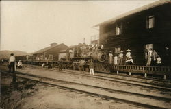Men and Women near a Freight Locomotive and Depot
