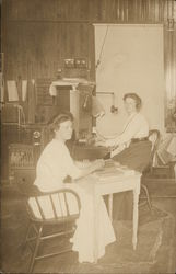Two Women in Office Setting with Switchboard