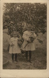 Two Young Girls in White Dresses, One Holding Kitten