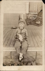 Boy with Feathered Headband Seated on Porch Holding Bird