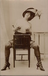 Topless Female in Garters, High-Heeled Boots, Seated and Holding Breasts