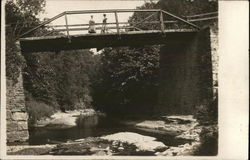 Two Women Standing on Bridge Above Tree-Lined Creek
