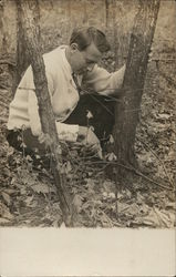 Man Kneeling By Tree