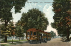 Two-Car Train in Street Beneath Trees, People Nearby