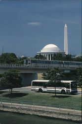 A Bus and a Train Cross with the Jefferson Memorial and Washington Monument in the Background