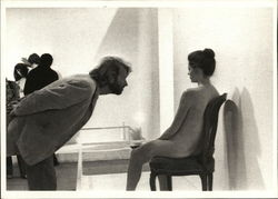 Photograph of Man Leaning Into a Nude Woman Seated