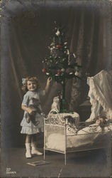 Little Girl Standing by Christmas Tree and Crib
