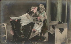 Two girls looking into a cradle with a Dog