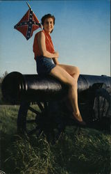 A Woman Sitting on a Canon Holding a Confederate Flag