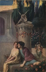 Man and Woman Sitting Close Together Near Column and Flowers