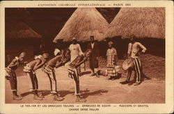 Four Native Dancers Posed, with Musicians Near Huts