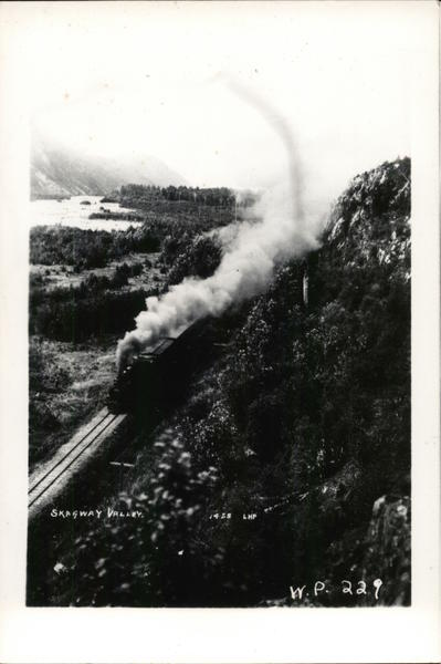 Train with Steam on Track in Mountainous Area, Aerial View Skagway Valley Alaska
