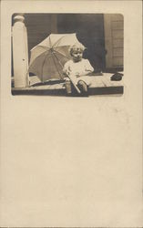 Baby Holding Umbrella on Porch