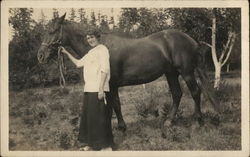Woman Holding Horse's Reins Near Trees