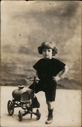 Portrait of Child With Toy Cart