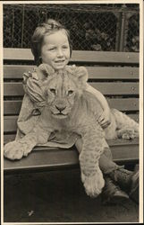 Girl with Lion Cub in Lap