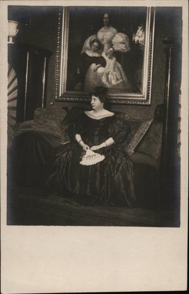 Woman Holding Fan Seated in Front of Portrait Women