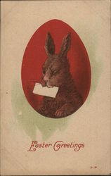 A bunny holding a letter painted on a red Easter egg