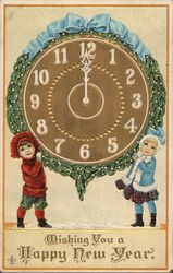 Two children holding up a clock striking midnight.