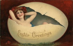 Woman draped in a blue cloth with brunette hair accented with red flowers sitting inside of a cracked eggshell grass with Easter Greetings written on its side.