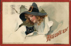 A beautiful witch and her black cat burst through a wall with Halloween written on it Postcard