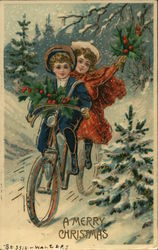 A young girl and boy ride a bicycle through the snow carrying holly branches