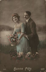 A moustached man stands behind a woman in a blue dress holding a flower arrangement with the caption Bonne fête below