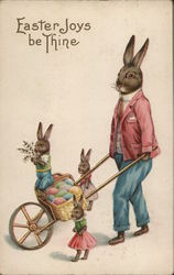 Easter Joys be Thine. Dad rabbit wearing a suit pushes a wheelbarrow of eggs. Three bunnies accompany.