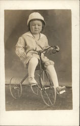 A Child Sitting on a Tricycle