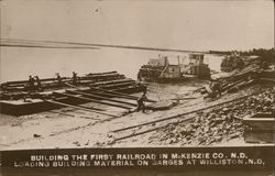 Building the First Railroad in McKenzie Co., Loading Building Material on Barges