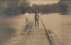 Two Men Standing on Flooded Train Tracks