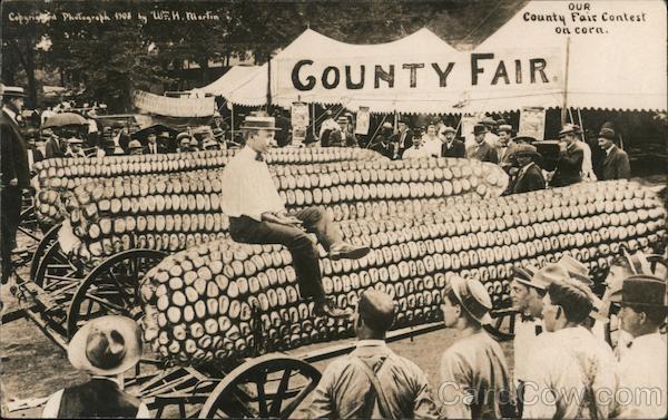 Our County Fair Contest on Corn - Man on Huge Ear of Corn