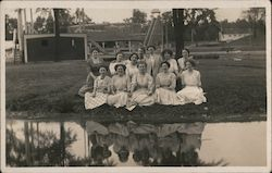 Group of Women Sitting on Lawn by Pond