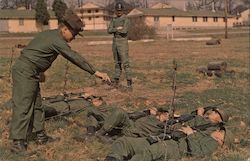 Basic trainees crawl under barbed wire in infiltration course exercise.