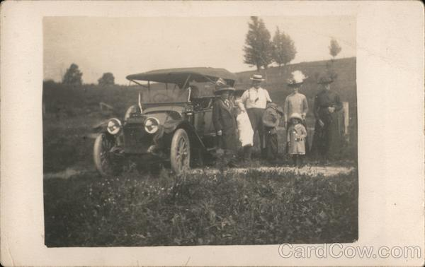 A Family Standing Next to a Car Cars