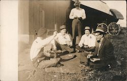Four Men Sitting on the Ground Playing Cards