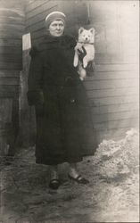 Woman in coat holding dog