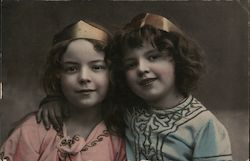 Two Little Girls Wearing Crowns with Their Arms Around Each Other