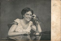 A Woman Sitting Talking on a Telephone