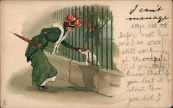 Woman in Green Coat and Red Hat With Umbrella Pets Dog Through Fence