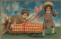 Thanksgiving Greetings - Person holding American flag while another is on a giant ear of corn.