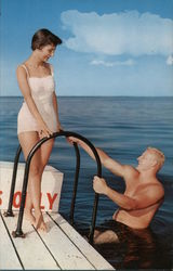 Man in water climbing up onto the dock toward a woman