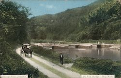 Color photograph of a bridge over a river with a horse drawn carriage on the road