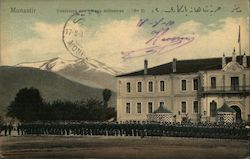 Military cadets lined up outside a school with a mountain in the distance