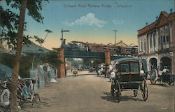 Train bridge crossing over a street with automobiles and horse carts