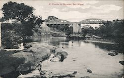 Photograph of a river with a bridge in the background